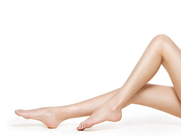 Belas pernas femininas após depilação isoladas em branco