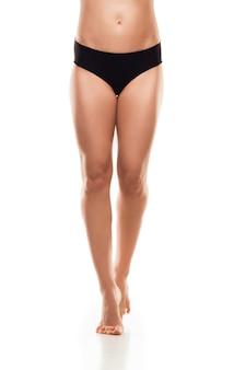 Belas pernas femininas, bumbum e barriga isoladas na parede branca.
