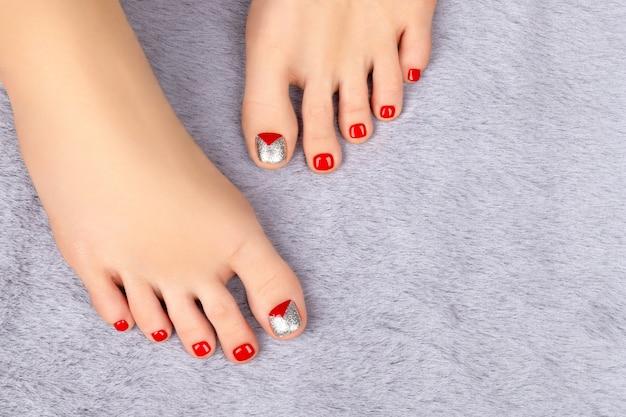 Belas pernas femininas com desenho de unhas no tapete cinza fofinho