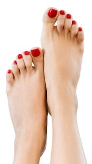 Belas pernas femininas com pedicure vermelha no fundo