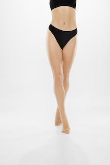 Belas pernas femininas e barriga isolada no branco.