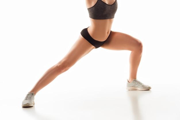 Belas pernas femininas e barriga na parede branca. conceito de beleza, cosméticos, spa, depilação, tratamento e fitness. fit e esportivo, corpo sensual com pele bem cuidada na cueca. treinamento.