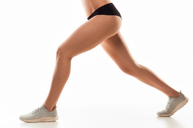 Belas pernas femininas e bumbum isolado na parede branca