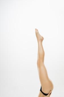 Belas pernas femininas e quadris isolados no branco