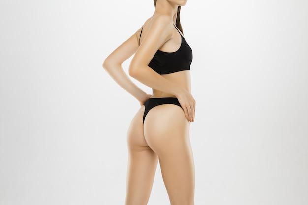 Belas pernas femininas e quadris isolados no fundo branco.