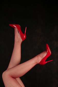 Belas pernas femininas em meias arrastão e sapatos vermelhos