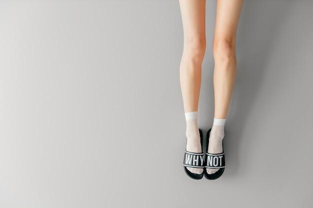 Belas pernas femininas em meias brancas e chinelos na moda