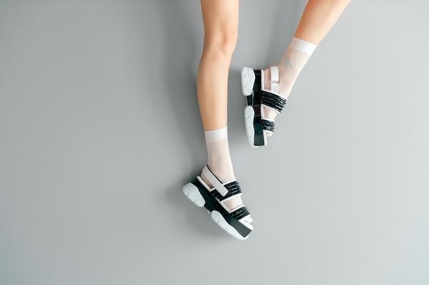 Belas pernas femininas em meias de malha branca na moda vestindo sandálias de couro preto branco cunha alta moda.