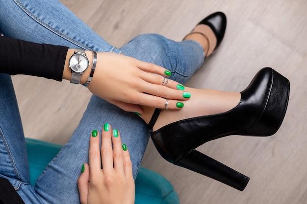 Belas pernas femininas em sapatos com mãos bem cuidadas