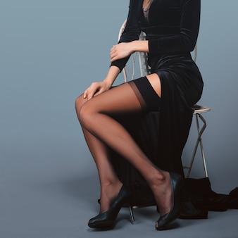 Belas pernas femininas em vestido de veludo longo com corte profundo e meias com cinto suspensor