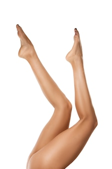 Belas pernas femininas isoladas na parede branca.