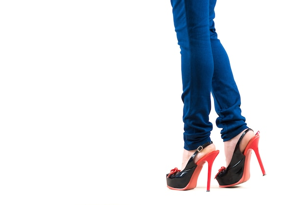 Belas pernas femininas magras com leggings de salto alto bege em uma parede branca