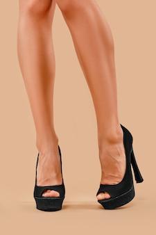 Belas pernas femininas magras com sapatos de salto alto