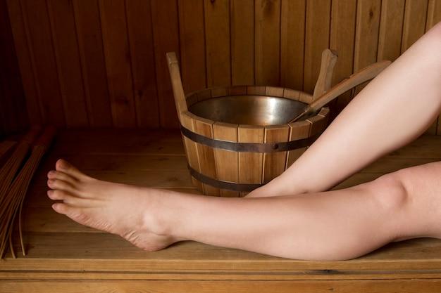 Belas pernas femininas na sauna, acessórios de banho. balde de madeira