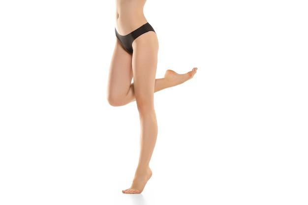 Belas pernas femininas, nádegas e barriga isoladas na parede branca, beleza
