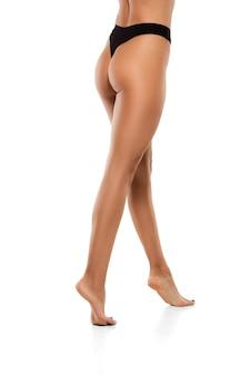 Belas pernas femininas, nádegas e barriga isoladas na parede branca