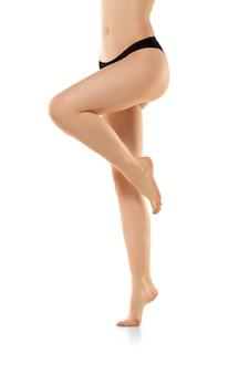 Belas pernas femininas, nádegas e barriga isoladas no fundo branco, corpo desportivo sensual com
