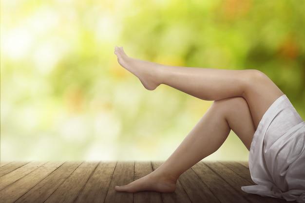 Belas pernas femininas no chão de madeira