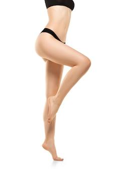 Belas pernas femininas, quadris e barriga isolados na parede branca, beleza