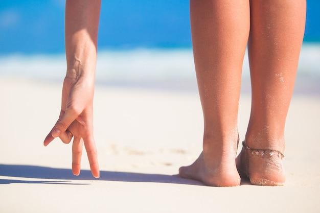 Belas pernas lisas das mulheres na praia de areia branca