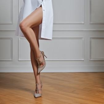 Belas pernas nuas femininas em roupa de médico.
