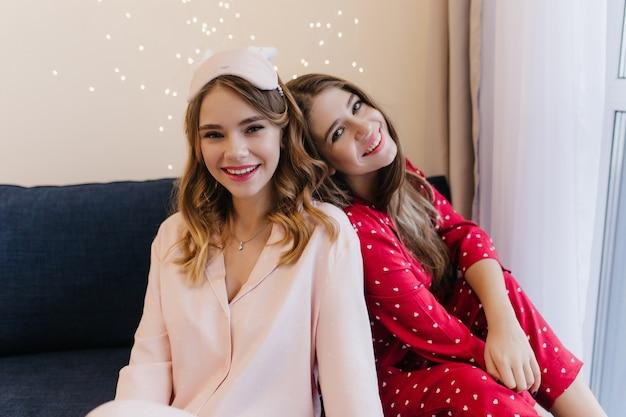 Belas senhoras caucasianas, passando a manhã no sofá. retrato interior de amigas sorridentes de pijama, posando no sofá aconchegante.