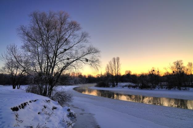 Belas vistas deslumbrantes do rio fundidas no início da primavera pelas árvores ao longo da costa em uma noite fria de primavera.