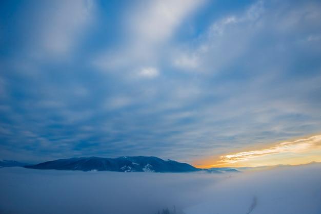 Belas vistas mágicas dos picos das montanhas estão localizadas entre a névoa e as nuvens cirros em uma noite quente de outono contra o pôr do sol