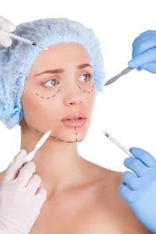 Beleza artesanal. mulher jovem assustada olhando para longe enquanto quatro mãos em luvas médicas segurando seringas e facas perto do rosto