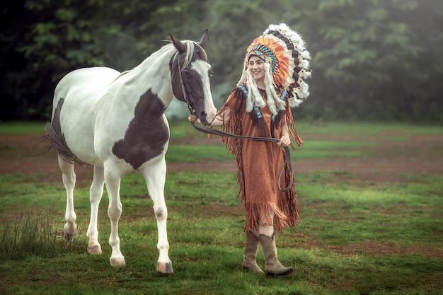 Beleza asiática jovem com maquiagem como mulher nativa americana e andando com cavalo de pintura americana na tailândia.