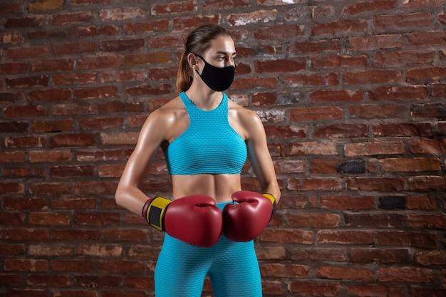 Beleza. atleta profissional treinando em fundo de parede de tijolo, usando máscara facial. esporte durante a quarentena da pandemia mundial de coronavírus. jovem mulher praticando no ginásio seguro usando equipamentos.
