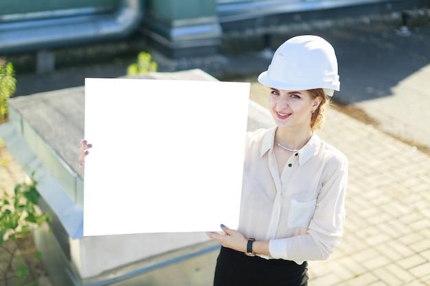 Beleza businesslady na blusa branca, relógio, capacete e saia preta ficar no telhado