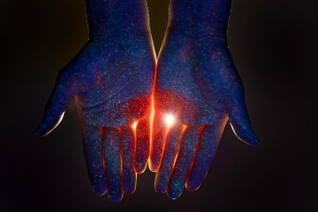 Beleza com as mãos na luz ultravioleta em gotas de tinta colorida. ilumine nas palmas das suas mãos, deus e religião. cosméticos para as mãos