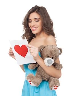 Beleza com cartão de dia dos namorados. mulher jovem e bonita lendo um cartão de dia dos namorados em pé, isolado no fundo branco