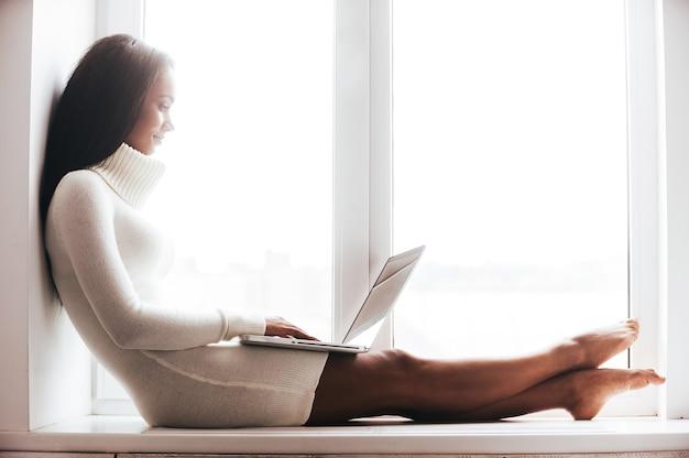 Beleza com laptop. mulher jovem e atraente africana com um agasalho quente trabalhando em um laptop enquanto está sentado no parapeito da janela