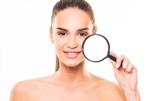 Beleza, conceito de produto de cuidado de pele. retrato de menina segurando a lupa sobre a pele do rosto.