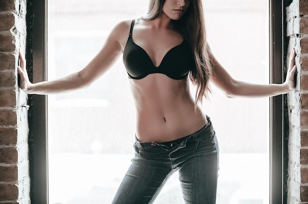 Beleza confiante. close de uma mulher jovem e bonita usando sutiã e calça jeans, mantendo os braços estendidos, em pé perto da janela