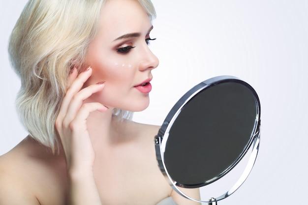 Beleza, cuidados com a pele e conceito dos povos - jovem mulher de sorriso que aplica o creme para enfrentar e olhar para espelhar em casa o banheiro.