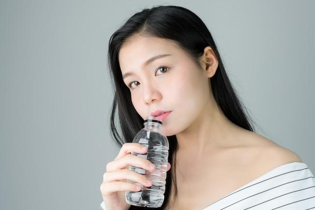 Beleza da pele da mulher e saúde, água potável de uma garrafa limpa.
