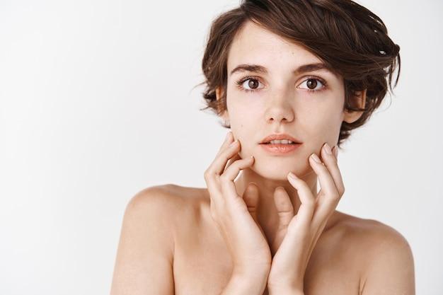 Beleza das mulheres. close de uma jovem com aparência natural sem maquiagem, tocando a pele hidratada suave, parecendo pensativa em pé sobre uma parede branca