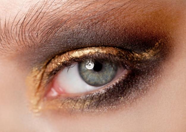Beleza de close-up de olhos com maquiagem criativa preto e dourado olhos esfumados cores