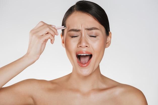Beleza de jovem estressada com cabelos castanhos, gritando de dor ao arrancar as sobrancelhas usando uma pinça, isolada sobre o branco