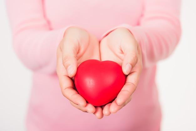Beleza de mulher com as mãos segurando um coração vermelho para ajudar doação de assistência médica