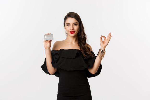 Beleza e conceito de compras. mulher linda em joias de luxo e vestido preto, mostrando o sinal de tudo bem e o cartão de crédito, em pé sobre um fundo branco.