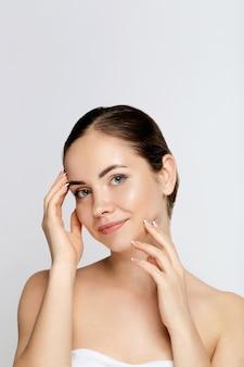 Beleza e conceito de spa. mulher jovem e bonita com pele limpa, fresca, toque no próprio rosto. tratamento facial. menina fêmea com maquiagem natural.cosmetologia. cuidados com a pele. cosméticos