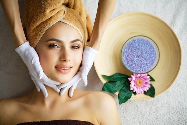Beleza e cuidado. cosmetologista faz massagem de rosto. mulher jovem