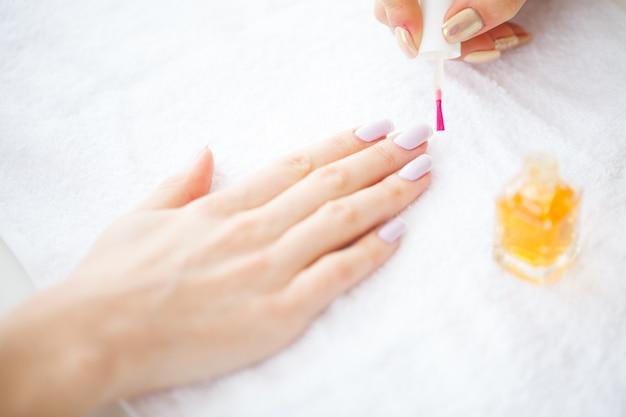 Beleza e cuidado. mãos de mulheres bonitas com manicure perfeita. manicure mestre aplicando esmalte em um salão de beleza. dia da beleza. spa manicure. cuidados com as mãos e unhas