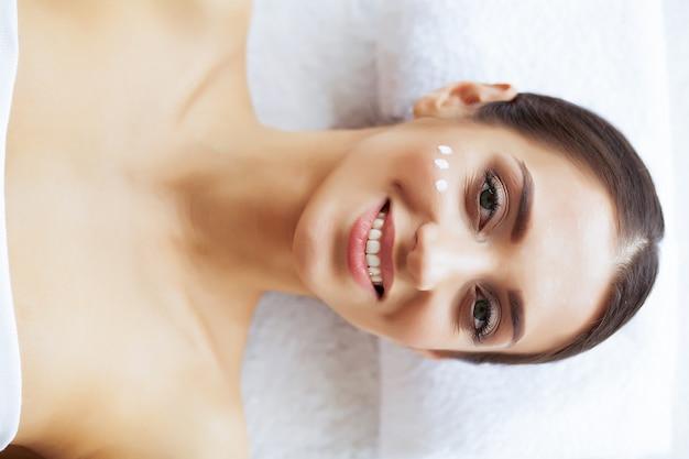 Beleza e cuidado. mulher no salão de beleza spa. moça que encontra-se em tabelas da massagem e que relaxa. pele pura e sorriso bonito. alta resolução