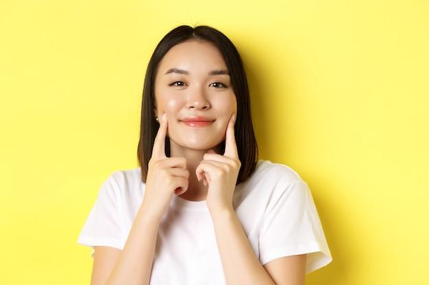 Beleza e cuidados com a pele. perto de uma jovem mulher asiática com cabelo escuro curto, pele saudável e brilhante, sorrindo e tocando covinhas nas bochechas, em pé sobre um fundo amarelo.