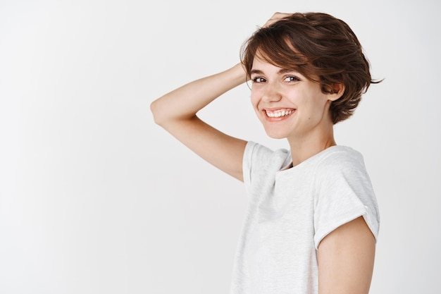 Beleza e cuidados com a pele. retrato de uma jovem autêntica com penteado curto bagunçado, tocando o cabelo e sorrindo feliz em pé na parede branca